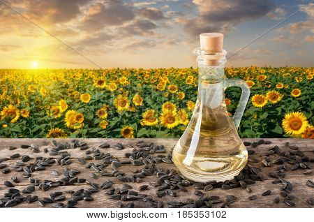 sunflower oil in glass bottle and scattered seeds on wooden table with blooming field on the background. Sunflower field on sunset. Photo with copy space. Agriculture and harvest concept