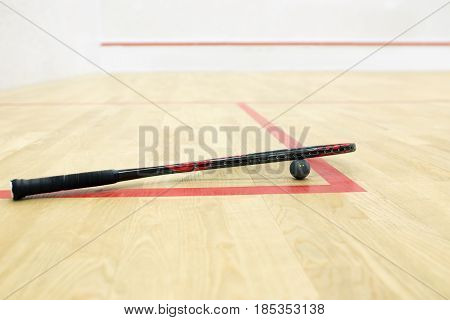 squash racket and ball on the court background. Racquetball equipment. Photo with selective focus