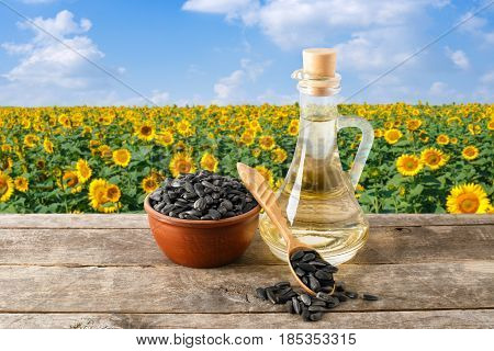 sunflower oil in glass bottle, seeds in bowl, spoon on wooden table with blooming field on the background. Sunflower field with blue sky. Photo with copy space. Agriculture and harvest concept