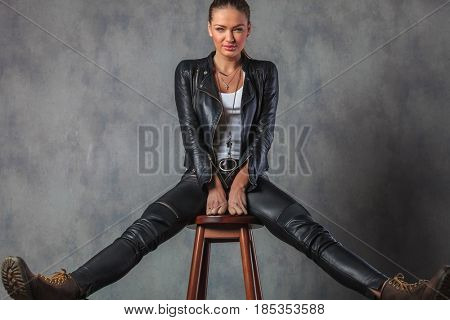 young woman in leather clothes and boots stretching her legs while sitting on stool in studio