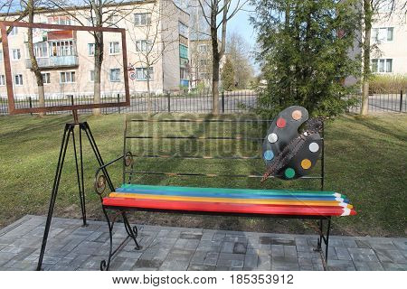 beautiful bench made like place for painting, pencils, brushes, colors and easel
