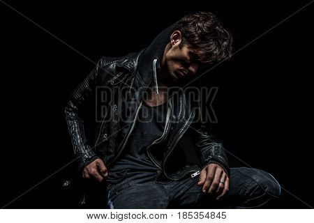side view of a man wearing hoodie and leather jacket looks down on black background