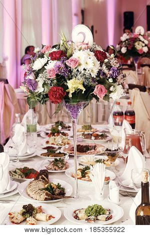 Flowers In Vases And Numbers Of Setting At Wedding Tables With Food In Restaurant, Luxury Wedding Re