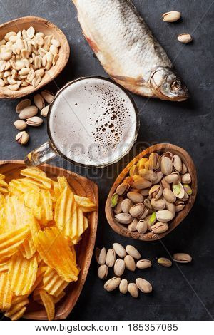 Lager beer and snacks on stone table. Nuts, chips, dry fish. Top view