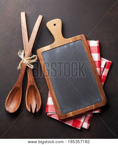 Cooking utensils on stone table. Top view with chalkboard for your recipe