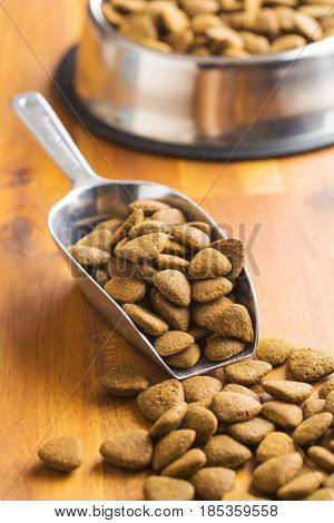 Dry kibble dog food in metal scoop on wooden table.