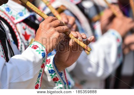People Singing At Traditional Wooden Flutes