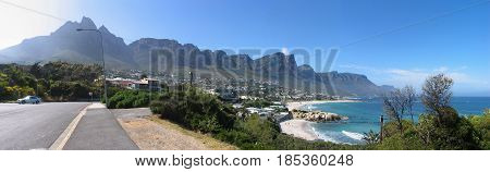FROM CAPE TOWN, SOUTH AFRICA, ROAD LEADING TO CAMPS BAY IN FORE GROUND AND  MOUNTAINS IN THE BACK GROUND,  WHICH ARE PART OF THE TABLE MOUNTAIN NATIONAL PARK