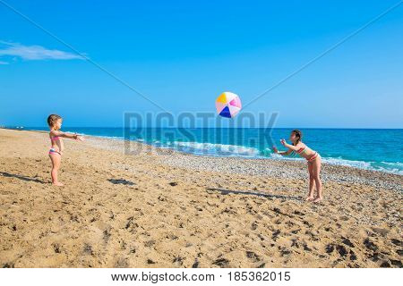 Children playing with a big ball on the beach. Summer vacation family vacation concept.