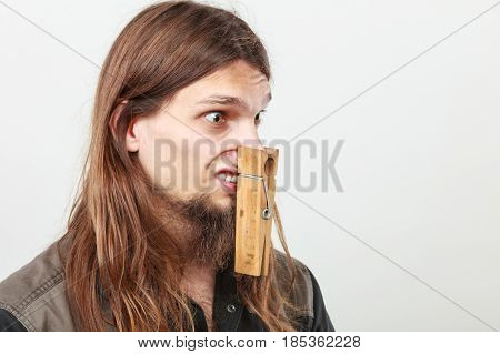 Unpleasant bad smell concept. Portrait of young long haired man with clogged nose by big clothespin.