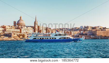 Valletta citiscape with bay cruise boat Malta