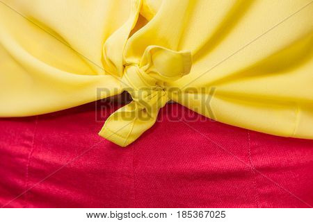Closeup girl wearing yellow knotted shirt and red shorts. Summer fashion.
