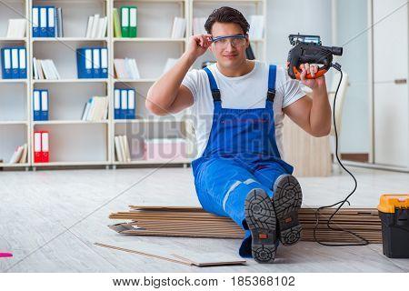 Young worker working on floor laminate tiles