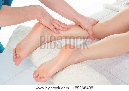 Sports Massage. Massage therapist working with patient massaging his calves. Close-up image.