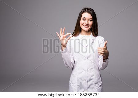 Cheerful Attractive Young Woman Doctor Holding A Pill And Showing Thumbs Up Over Grey Background.
