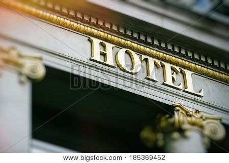 Sun flare above hotel word with golden letters on luxury hotel with beautiful columns