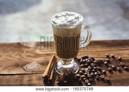 Cappuccino and coffee beans cinnamon. background Roasted coffee beans close-up. Coffee beans with space for text. Seasoning. Spices. Cinnamon. Badian. Coffee house. Latte. Cappuccino.