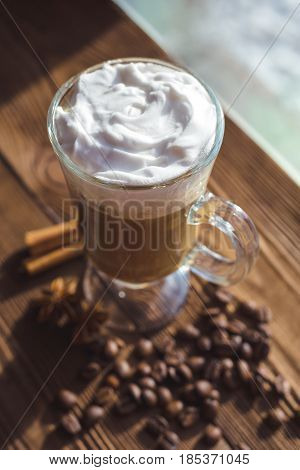 Cappuccino And Coffee Beans, Cinnamon. Background Roasted Coffee Beans Close-up. Coffee Beans With S