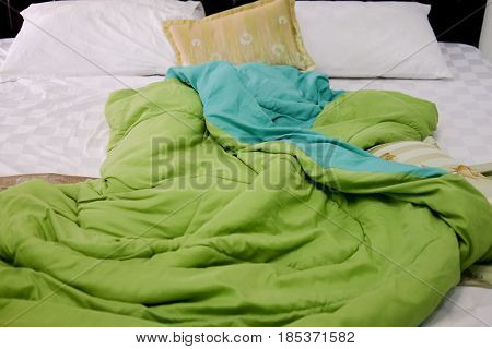 Green duvet and whie pillows on an unmade bed
