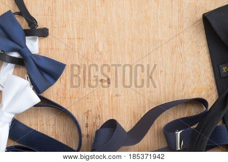 Set of man's accessories (bowtie and necktie) on wood table with copy space