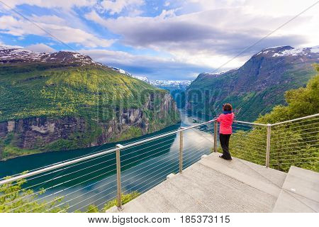 Tourism vacation and travel. Female tourist enjoying beautiful view over magical Geirangerfjorden from Flydalsjuvet viewpoint taking photo with camera Norway Scandinavia.