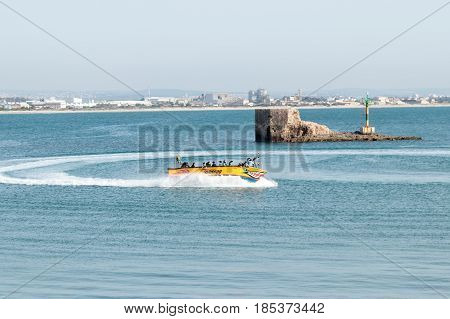 Tourists Ride On A Multi-seater Motor Boat On The Mediterranean Sea Near The Walls Of The Old City O
