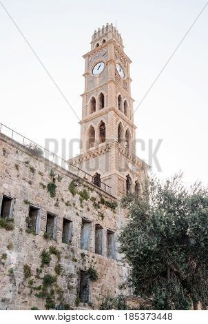 Abandoned building of caravanserai Khan al-Umdan and the clock tower Khan al-Umdan in the old town of Ako Israel