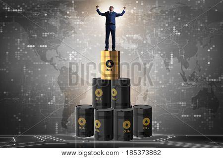 Businessman on top of oil barrels