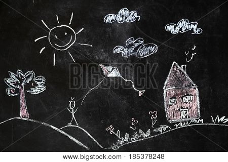 children's chalk drawing of house and sun on black background the concept of nature and the environment