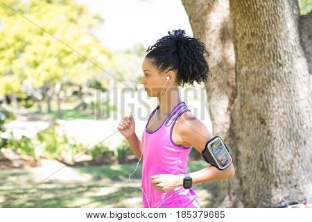 Female jogger listening to music while jogging in the park on a sunny day