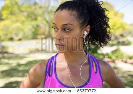 Close-up of jogger woman listening to headphones in the park