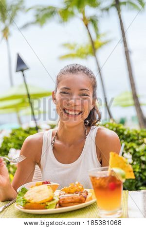 Happy woman at restaurant eating Hawaii burger with pineapple and karaage fried chicken. Hawaiian japanese fusion food. Asian girl at hotel restaurant table during summer travel vacation.