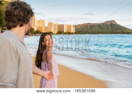 Couple relaxing holding hands having fun on Waikiki beach Hawaii vacation. Happy tourists people in love walking at sunset on popular travel destination in Honolulu, Oahu, Hawaii.