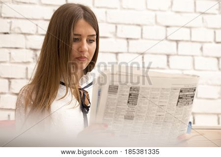 Young Serious Woman Read The Latest News In The Newspaper