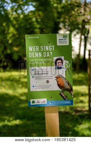 Regensburg,Germany-May 7,2017: A sign in park invites people to identify a bird by recording its song on their mobile phones and sending via text message to a number where an expert will identify it and reply