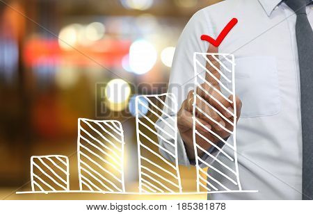 Hand of businessman use finger touch top bar graph in icon Check mark for idea presentation in your organization and work.