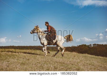 Man galloping on white horse