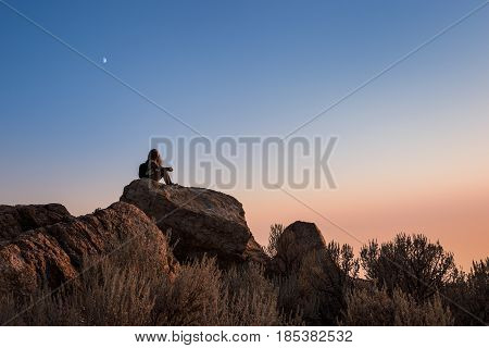 Sunset at the top of Antelope Island with silhouette of female sitting on rocks near Salt Lake City Utah with moon