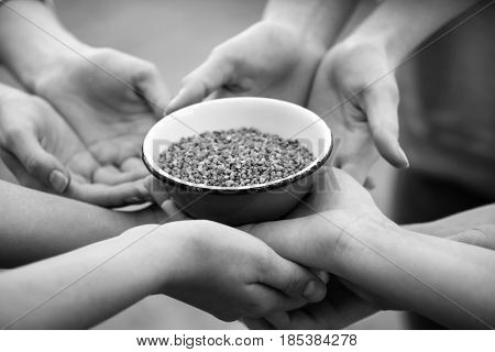 Poor people holding bowl with buckwheat