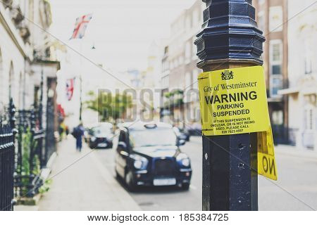 LONDON UK - August 02 2014: road sign in London with architecture an taxi cab bokeh in Mayfair