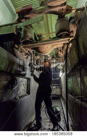 Nizhny Novgorod, RUSSIA - MARCH 19, 2017: Workers car mechanics make repairs of trucks in the indoor hangar. Russia.