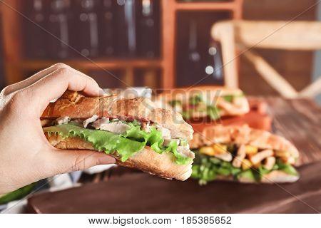 Female hand holding croissant bun with chicken salad