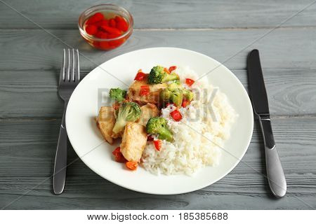 Chicken stir fry with rice and cutlery on table