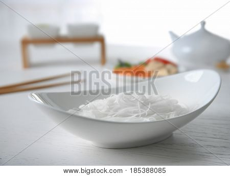 Rice noodle in white plate against light blurred background