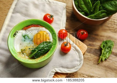 Portion of baked eggs Florentine on wooden kitchen table