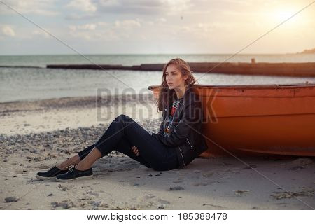 A girl sideways sitting near a red boat on the beach by the sea with beautiful sunset on the background. Woman in jeans pullover and jacket on the sand