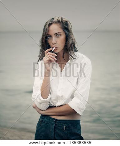 Beautiful business woman in white shirt and pants smokes a cigarette on the beach near the sea.