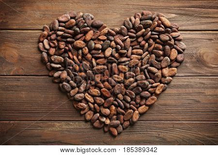 Heart made of aromatic cocoa beans on wooden background