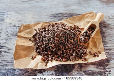 Heap of aromatic cocoa nibs and scoop on wooden table