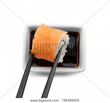 Dipping tasty roll into bowl with soy sauce on white background